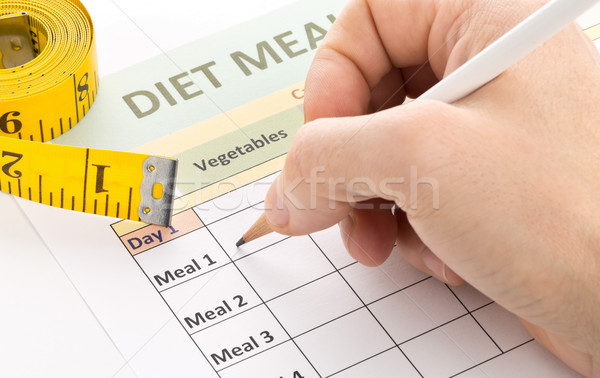 Dieting weight loss concept - man filling out diet planning form Stock photo © ShawnHempel