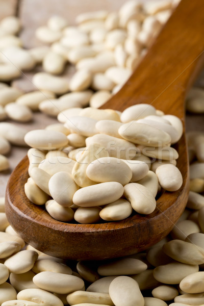 Dry white bean legumes in wooden spoon Stock photo © ShawnHempel