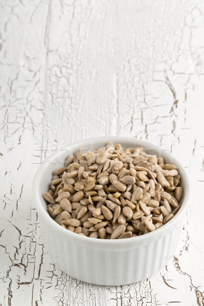 Shelled sunflower seeds in bowl on rustic white table Stock photo © ShawnHempel