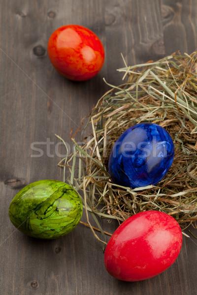 Easter eggs in hay nest on dark wood Stock photo © ShawnHempel