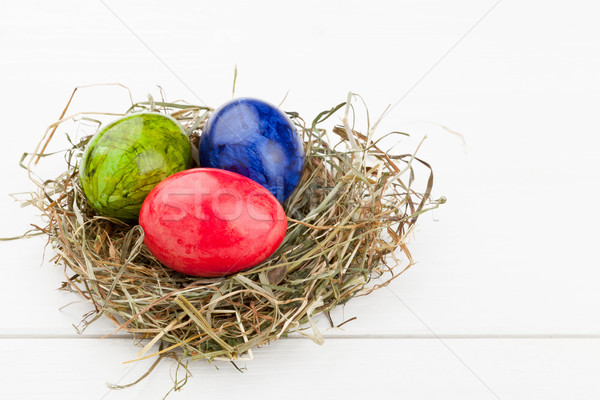 Easter eggs in hay nest on white wood Stock photo © ShawnHempel