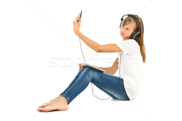 Young girl sitting on the floor taking a selfie with headphones Stock photo © ShawnHempel
