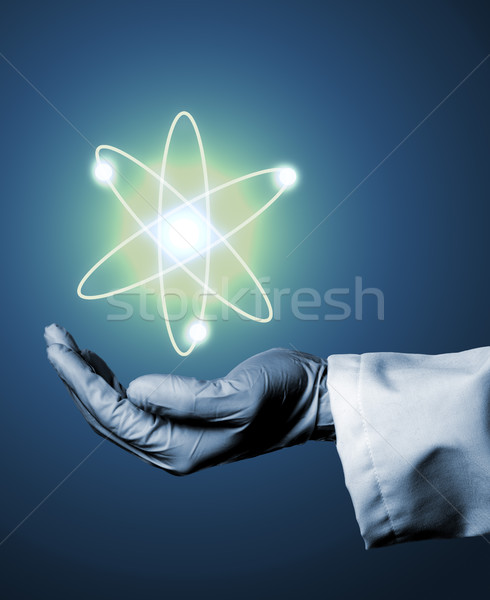 Researcher or scientist with rubber glove holding glowing atom m Stock photo © ShawnHempel