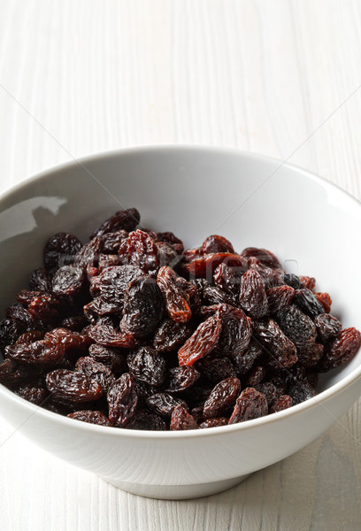 Organic raisins in white bowl Stock photo © ShawnHempel
