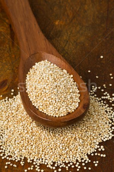 Raw, whole, unprocessed quinoa seed in wooden spoon on wood boar Stock photo © ShawnHempel