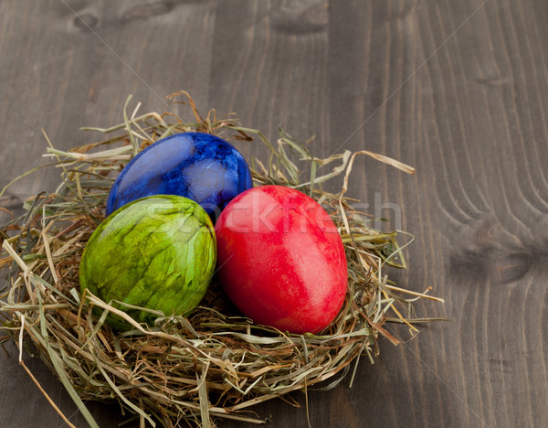 Easter eggs in hay nest on dark wood Stock photo © ShawnHempel
