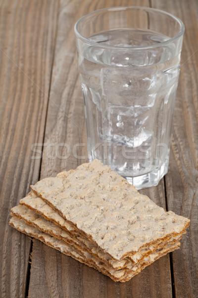 Wheat crispbread slices and glass of water Stock photo © ShawnHempel