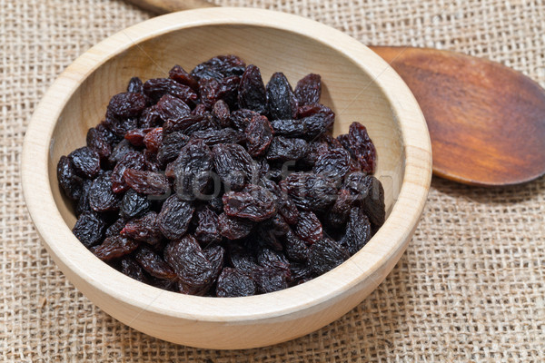 Organic raisins in wooden bowl with spoon Stock photo © ShawnHempel