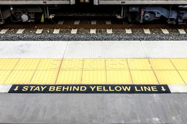 Tartózkodás mögött citromsárga vonal figyelmeztető jel vasútállomás Stock fotó © silkenphotography