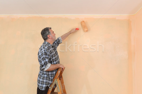 Adult worker paint wall in a room to orange Stock photo © simazoran