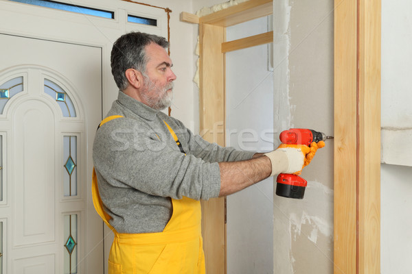 Construction site, worker installing gypsum board using electric Stock photo © simazoran