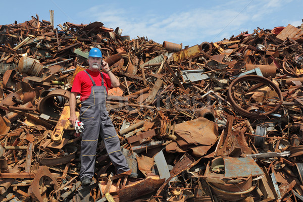 Recycling industry, worker using phone at heap of old metal Stock photo © simazoran
