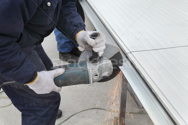 Worker using angle grinder, construction site Stock photo © simazoran