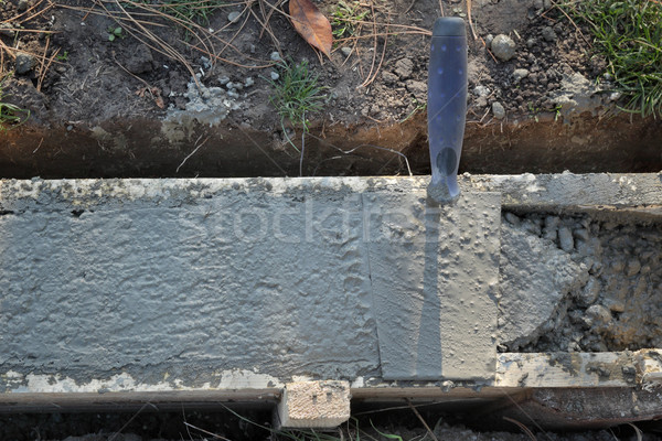 Trowel at wall foundation, concrete in formwork and tool Stock photo © simazoran