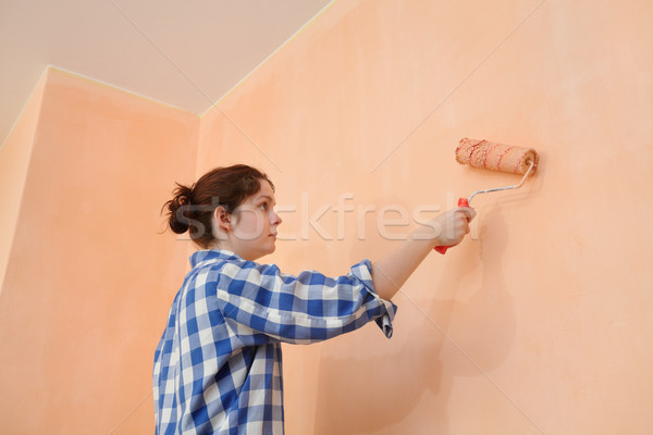 Young worker paint wall in a room to orange Stock photo © simazoran
