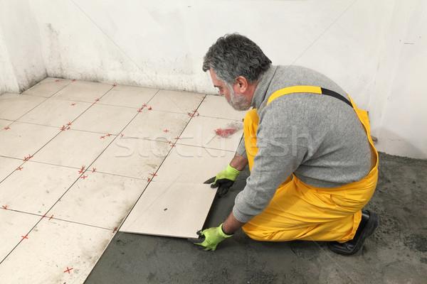 Home renovation, worker placing tile Stock photo © simazoran