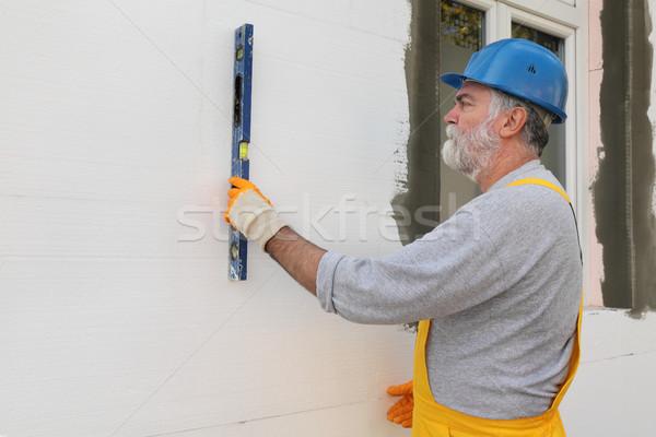 House renovation, polystyrene wall insulation, level tool Stock photo © simazoran