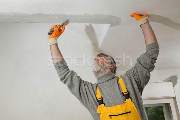 Worker repairing plaster at ceiling Stock photo © simazoran