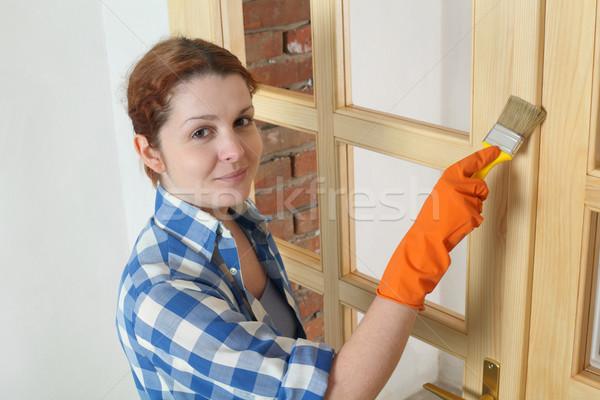 Young girl worker, painting new wooden door Stock photo © simazoran