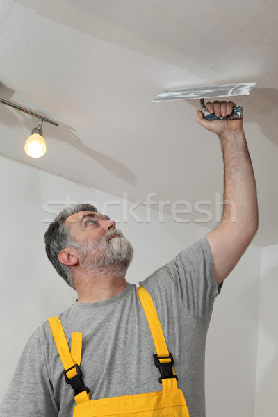 Home renovation, worker repairing plaster at ceiling Stock photo © simazoran