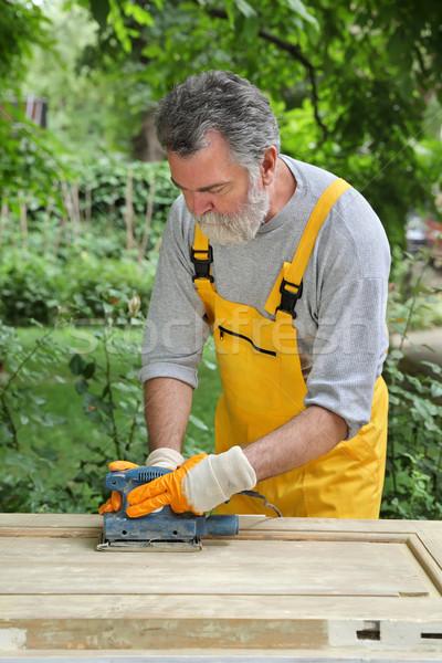 Home renovation, sanding wooden door Stock photo © simazoran