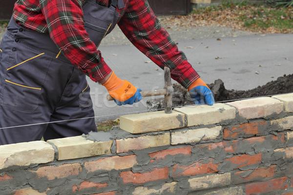 Worker building brick wall using hammer Stock photo © simazoran