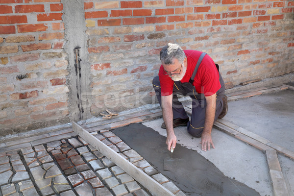Pavement or terrace making, worker spreading mortar Stock photo © simazoran