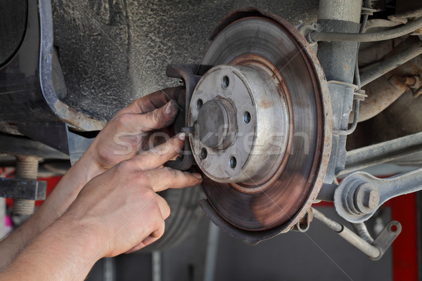 Stock photo: Car mechanic working on disc brakes