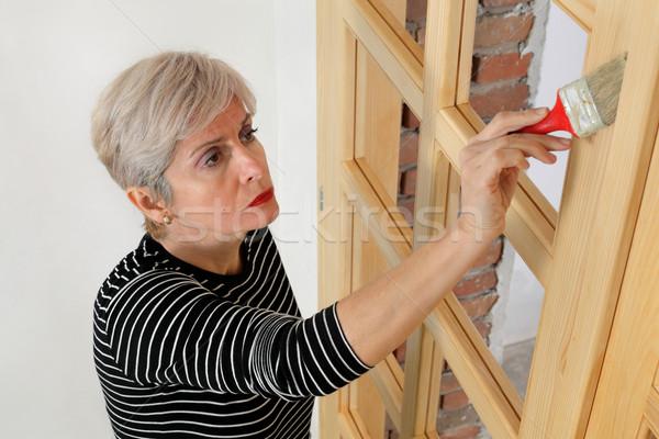 Adult female worker painting  wooden door Stock photo © simazoran