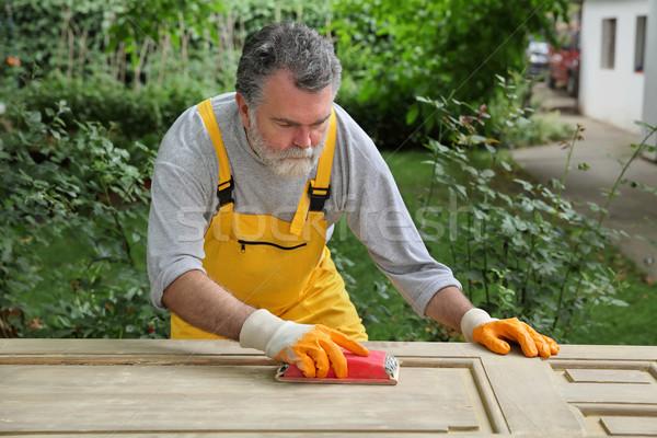 Home renovation, worker sanding wooden door Stock photo © simazoran