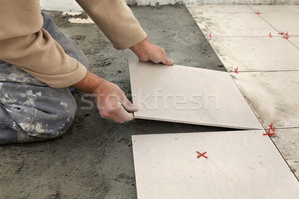 Home renovation, worker placing tile Stock photo © simazoran