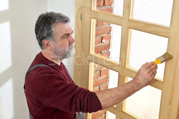 Home renovation, worker painting wooden door, varnishing  Stock photo © simazoran