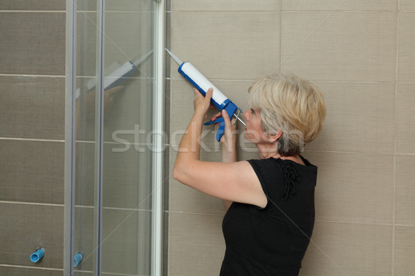 Home renovation, shower cabin fixing with silicone Stock photo © simazoran