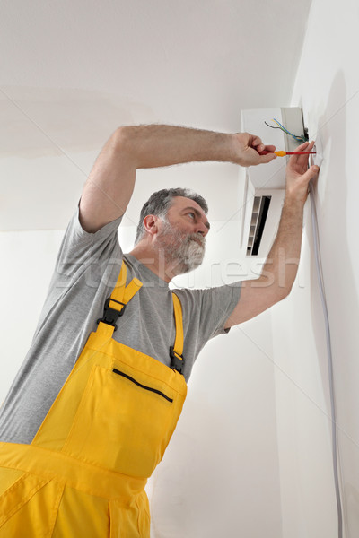 Electrical installation of air conditioner, electrician at work Stock photo © simazoran