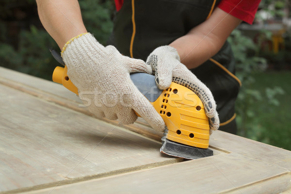 Home renovation, worker sanding wooden door Stock photo © simazoran