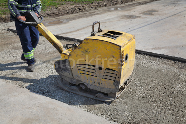 Worker use vibratory plate compactor at road construction site Stock photo © simazoran