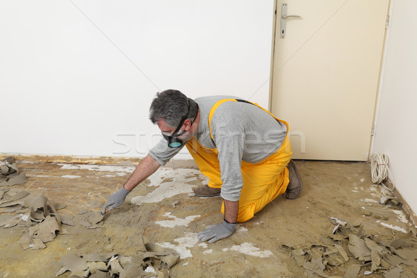 Worker using putty knife for cleaning floor Stock photo © simazoran
