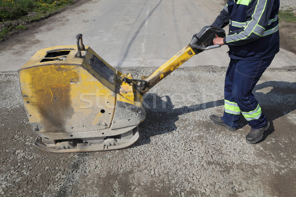 Stock photo: Worker use vibratory plate compactor at road construction site