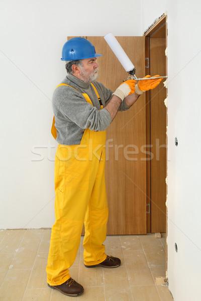 Worker installing wooden door, using polyurethane foam Stock photo © simazoran