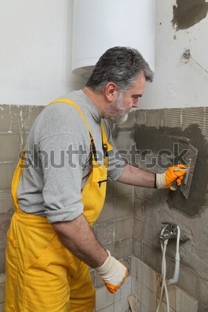 Worker caulking bath tube and tiles Stock photo © simazoran