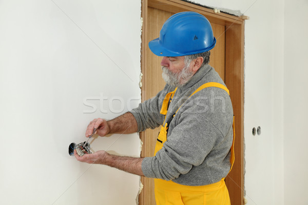 Electrician at construction site install electrical plug Stock photo © simazoran