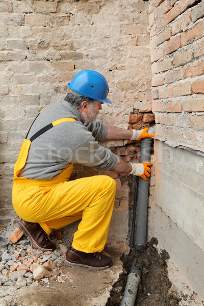Plumber at construction site installing sewerage tube Stock photo © simazoran
