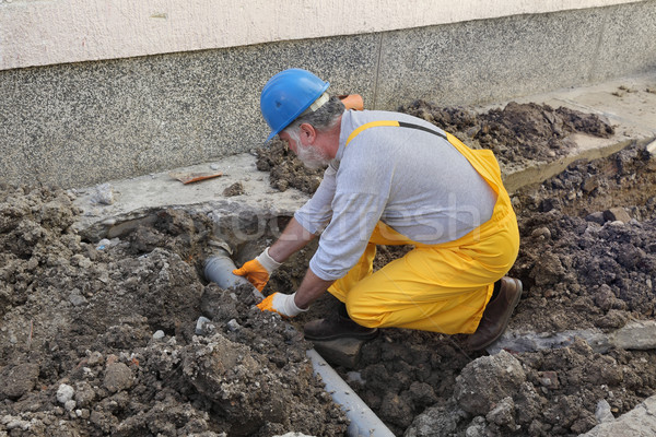 Plumber at construction site repair sewerage tube Stock photo © simazoran