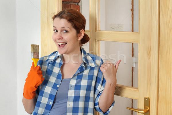 Young smiling girl worker, painting new wooden door Stock photo © simazoran