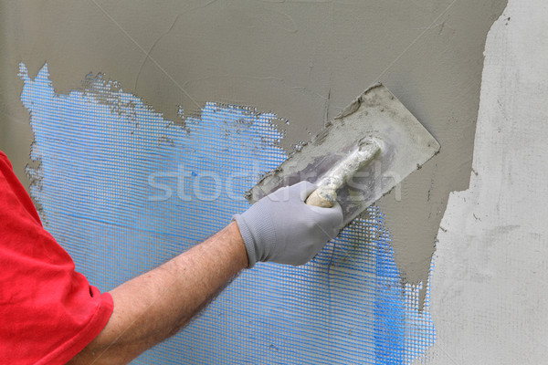 Wall insulation, spreading mortar over mesh Stock photo © simazoran