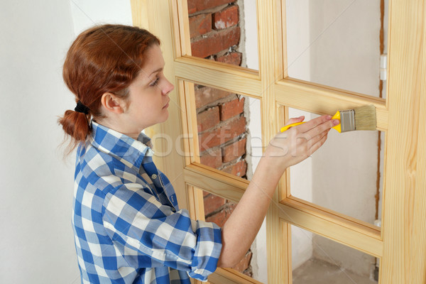 Young girl worker, painting new wooden door Stock photo © simazoran