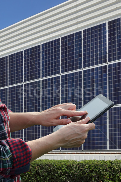 Solar energy, worker hands using tablet and panels Stock photo © simazoran
