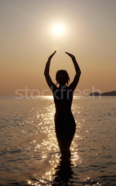 Sziluett fiatal gyönyörű lány naplemente vízpart tengerpart Stock fotó © simazoran