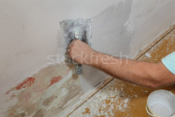 Stock photo: Worker spreading plaster to damaged wall