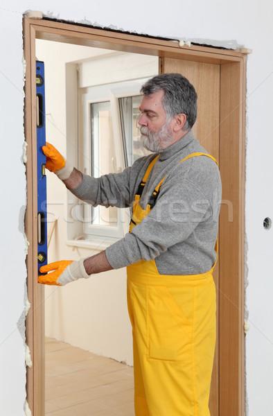 Builder measure verticality of door with level tool Stock photo © simazoran